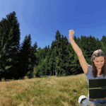 """Photoshopped image shows an excited young woman with her hands up in the air. She is sitting cross-legged with a laptop on her lap. She has been photoshopped into a field in front of an evergreen forest. This is the featured image for a blog post titled """"What is Evergreen Content and Why Do Nonprofits Need It?"""""""