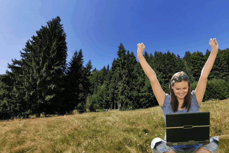 "Photoshopped image shows an excited young woman with her hands up in the air. She is sitting cross-legged with a laptop on her lap. She has been photoshopped into a field in front of an evergreen forest. This is the featured image for a blog post titled ""What is Evergreen Content and Why Do Nonprofits Need It?"""