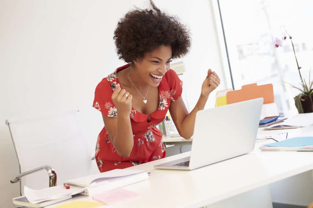 Photo shows a happy, excited woman standing behind her desk, looking at her laptop screen. This is the featured image for a blog post about free blogging tools to help make your posts shine.