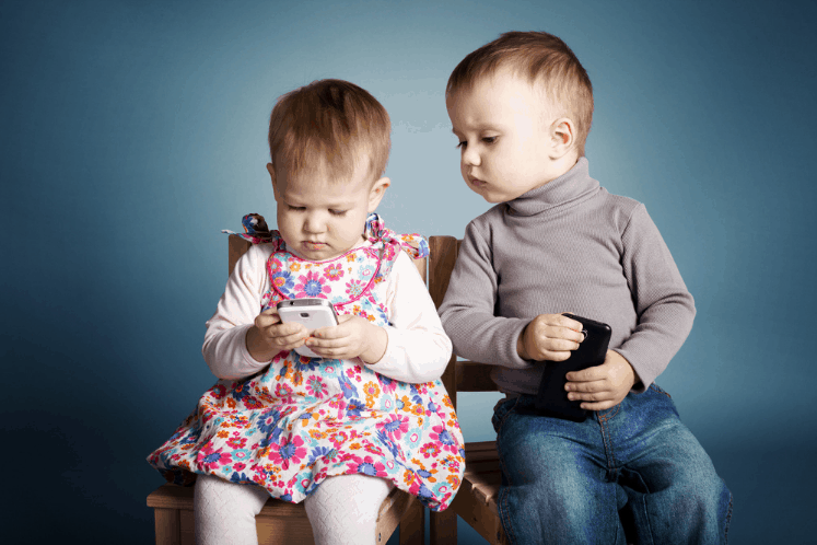 This is a post about social media engagement. The featured image is a photo of two toddlers, a boy and a girl. They're sitting together on a bench. Both have cell phones. She is looking intensely at the screen of her phone while he looks worriedly over her shoulder, trying to peek