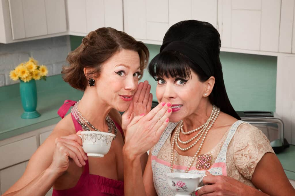 Photo of two women dressed in retro 1950s outfits. They're in a kitchen, sipping tea and one woman is whispering a secret to the other. The purpose of the photo is to make you think of etiquette because the post is about the rules of social media and why etiquette matters.