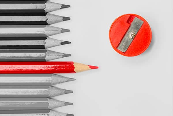 Red pencil next to grey pencils and red sharpener