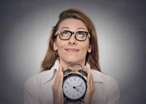 Business woman in black glasses looking hopefully up at the sky while holding a traditional looking alarm clock between her hands