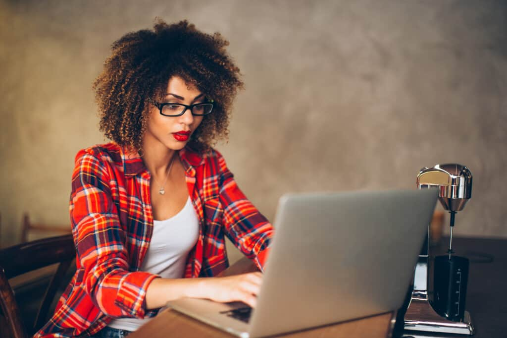 Photo shows an attractive young woman, mid 20s, African American. She is wearing a red plaid shirt, sleeves rolled up. She is sitting at a table, looking very focused as she works on her laptop.