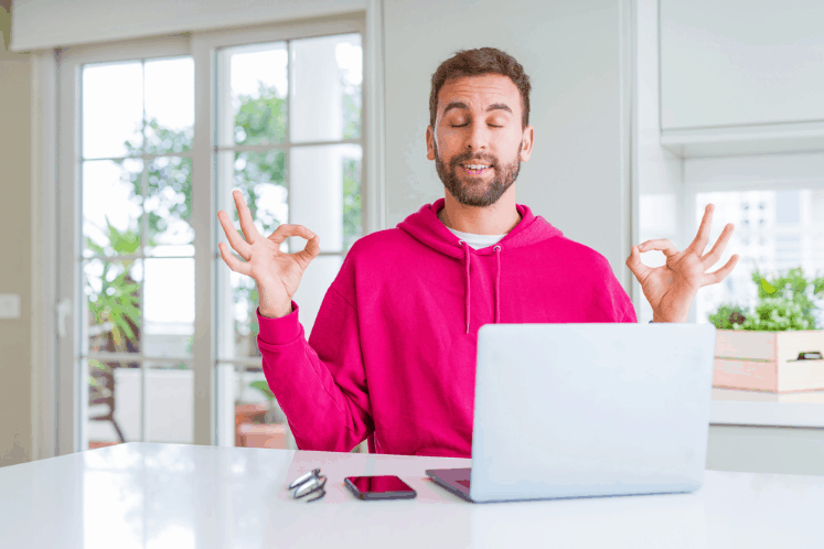"""Young man with beard meditating at his desk. He is wearing a hot pink hoodie and the desk and surrounding area are very clean and tidy. There is a laptop, phone and pen on the desk, neatly arranged. This is the featured image for a blog post titled """"How to Marie Kondo Your Nonprofit Website So Great Content Can Shine"""