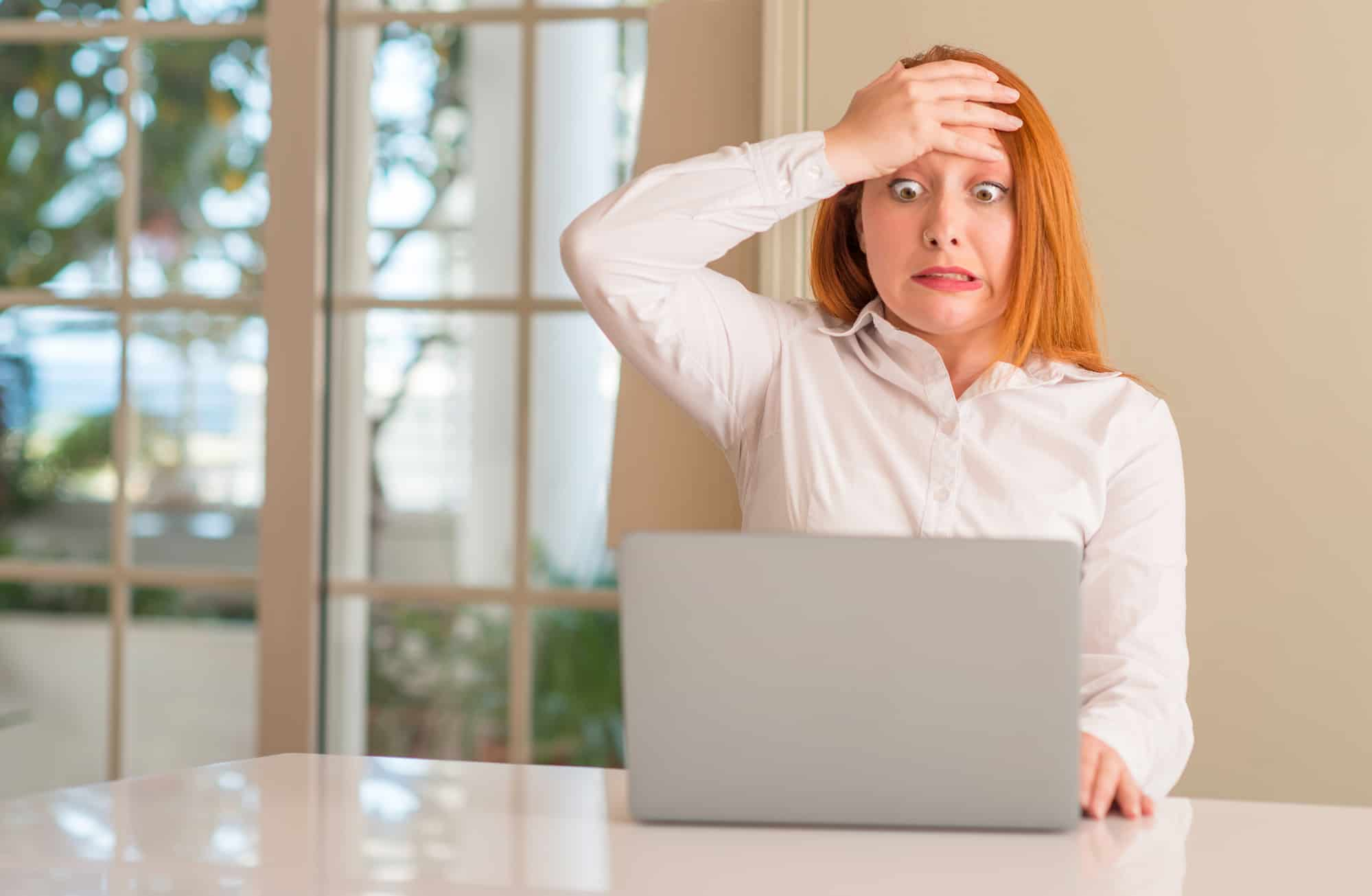 Mid 30s caucasian woman with long read hair, wearing a white shirt. She is stressed out, with one hand slapped against her forehead as she looks down at her laptop screen. This is the featured image for an article about Website Design Mistakes.