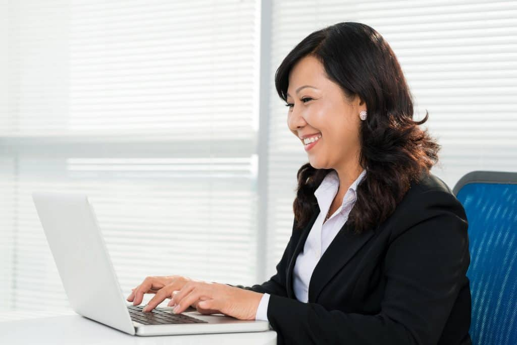 Smiling Business Woman is working on her laptop.