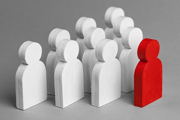 Red wooden person figure training a group of white wooden people figures