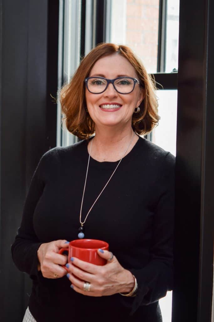 Photo of Kim Scaravelli. She is smiling, middle-aged woman with shoulder length brown hair. Has large, blue rimmed glasses on. Wearing a black sweater and holding a red coffee mug.