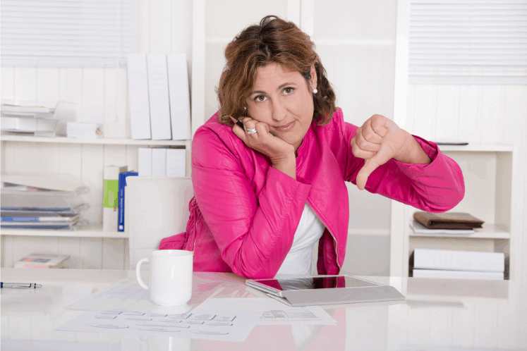 "Photo shows an woman in a bright pink blazer, sitting at her desk. She is frowning and giving the thumbs down with her left hand. This is the featured image for a post titled ""Nonprofit Branding: No One Cares About Your Logo"""