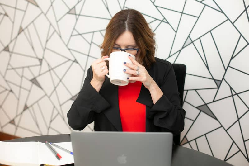 Kim Scaravelli behind her office desk drinking large cup of coffee